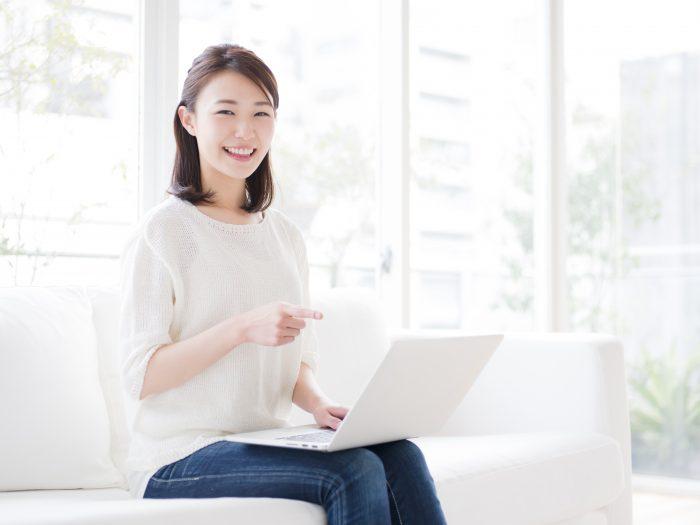 笑顔でパソコンを指差す女性