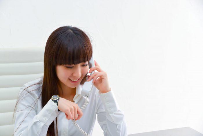 固定電話で電話をかける女性